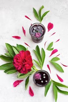 Agua de flor de jamaica tea with magenta peony flower and petals