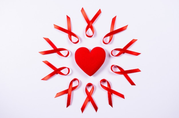 Aids awareness red ribbon around red heart on white background