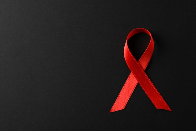 Aids awareness red ribbon on black wall, space for text