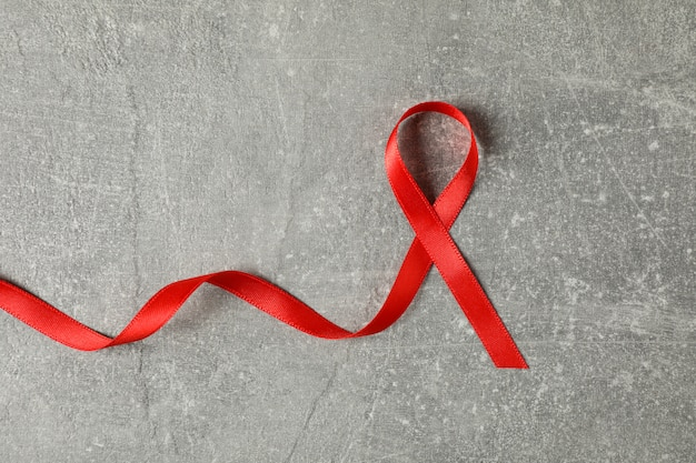 Aids awareness red ribbon on grey wall, space for text