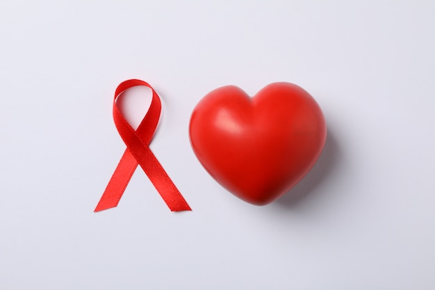 Aids awareness red ribbon and heart on white wall, space for text