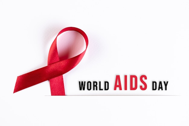 Aids awareness red ribbon on white paper with text. world aids day concept.