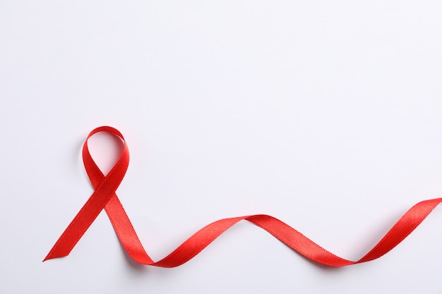 Aids awareness red ribbon on white wall, space for text