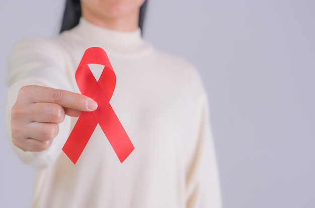 Aids red ribbon in woman's hand for world aids day and national hiv/aids and aging awareness month concept. copy space.