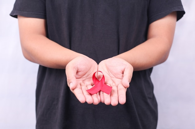 Aids symbol with red ribbon in hand isolated on white background