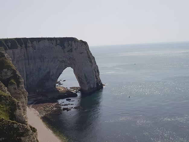 프랑스의 햇빛 아래 바다로 둘러싸인 aiguille d' etretat