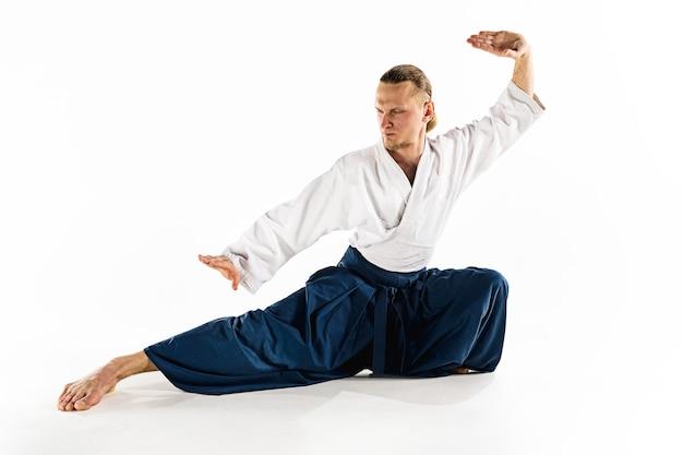 합기도 마스터는 방어 자세를 연습합니다. 건강한 생활 방식과 스포츠 개념입니다. 흰색 바탕에 흰색 기모노에 수염을 가진 남자. 제복에 집중된 얼굴을 가진 가라테 남자.