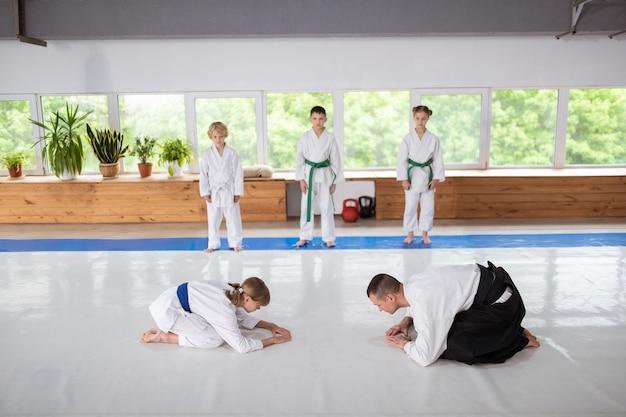 Тренер по айкидо и девушка приветствуют перед практикой айкидо