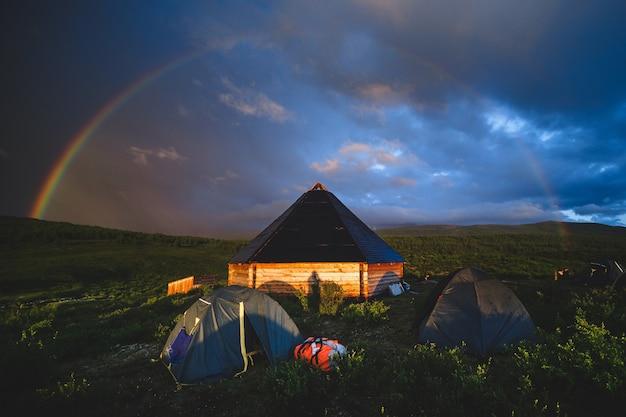 Традиционный алтайский домик и туристические палатки под радужным куполом в онгудайском районе республики алтай, россия.