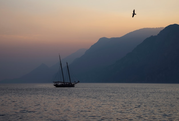 Ailboat sailing at sunset on the background of a mountain range