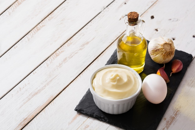 Aioli sauce and ingredients on white wooden table copy space