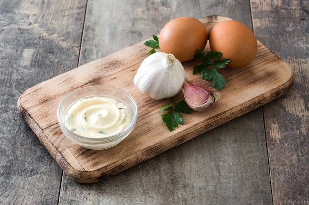 Aioli sauce and ingredients on wooden tabe