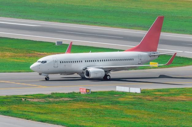 Самолет на взлетно-посадочной полосе после приземления, руление до терминала в аэропорту.