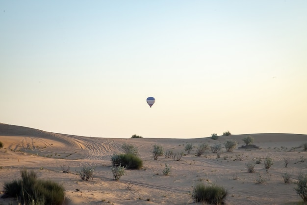Air balloon flying over sandy dunes with clear blue sky
