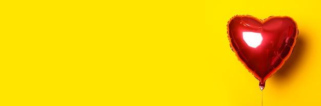 노란색 바탕에 심 혼의 형태로 공기 풍선. 배너.
