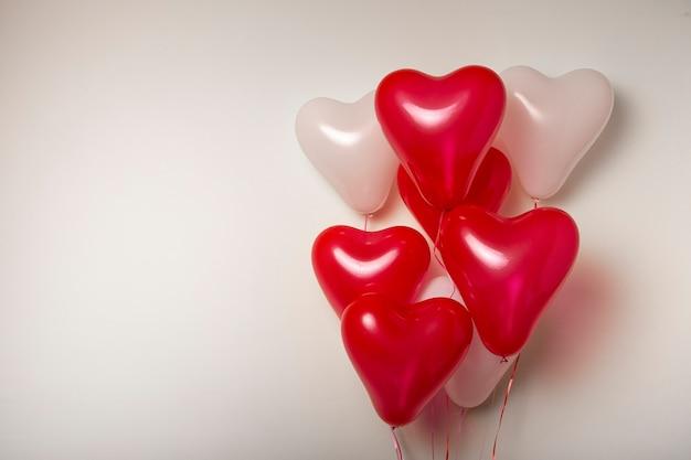 공기 풍선. 빨간색과 흰색 심장의 무리 모양의 흰색 바탕에 풍선. 발렌타인 데이 장식.