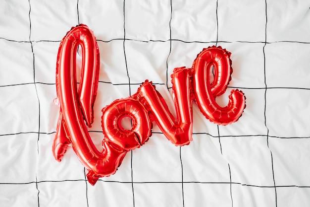 Воздушные шары в форме слова «любовь» на кровати. концепция любви. праздник, торжество. день святого валентина или украшение свадьбы / девичника. воздушный шар из красной фольги