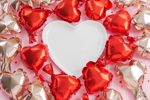 Воздушные шары из фольги в форме сердца вокруг белой тарелки в форме сердца.