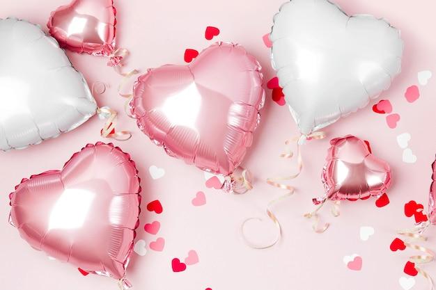 Воздушные шары из фольги в форме сердца на пастельно-розовом фоне. концепция любви. праздник. день святого валентина или украшение свадьбы / девичника. металлический шар