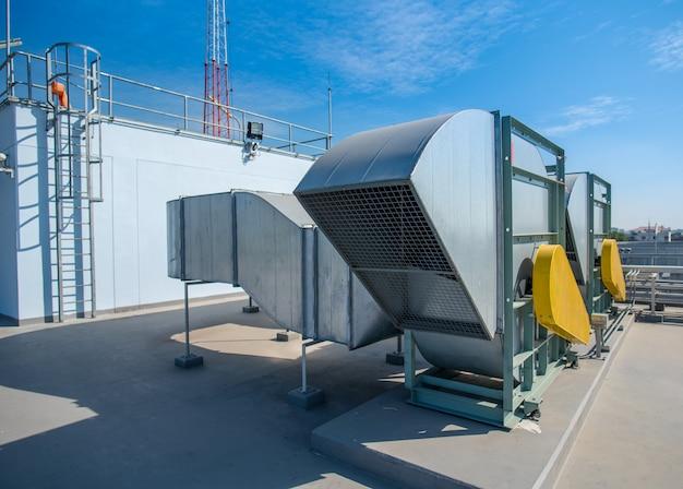上空の背景を持つ屋上デッキのエアコンシステムの空気圧縮機機械部品。
