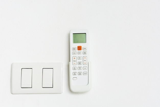 Air-condition and light switch on white background with copy space