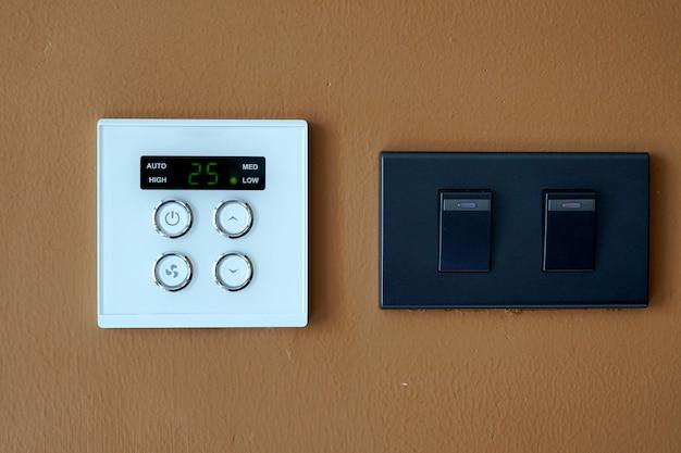 Выключатель кондиционера и выключатель освещения на коричневом фоне стены