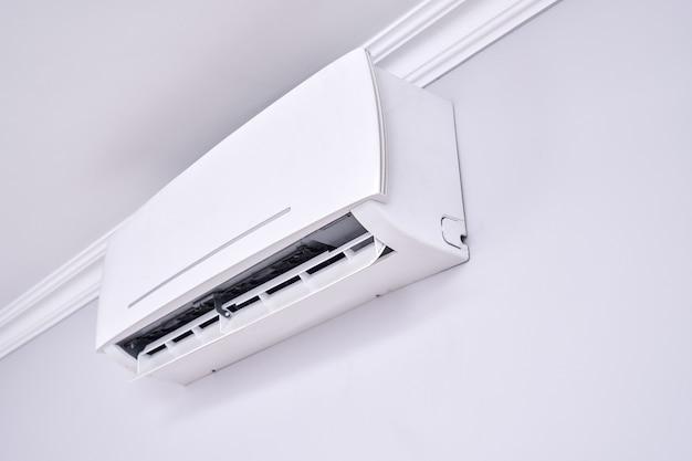 屋内の白い壁に隔離されたエアコンをクローズアップ