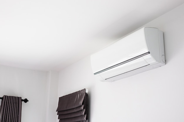 Air conditioner on white wall room interior