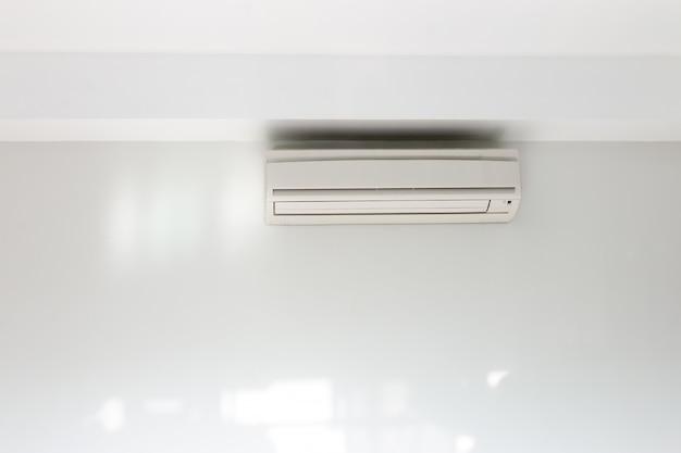 집안의 흰 콘크리트 벽에 설치된 에어컨