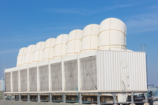 Air cooling tower for hvac chilling units at building rooftop outdoor blue sky.