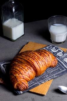Croissant all'aria con sciroppo di fragole e bicchiere di latte
