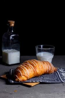 Cornetto all'aria con crema bianca in cima e un bicchiere di latte