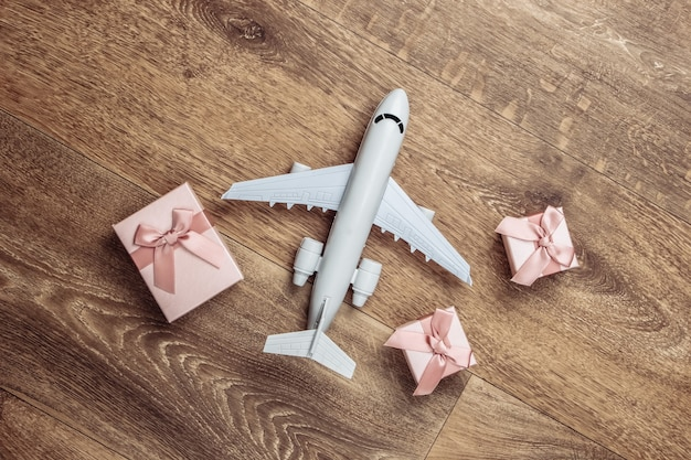 Air delivery. plane figurine and gift boxes on floor. flat lay.