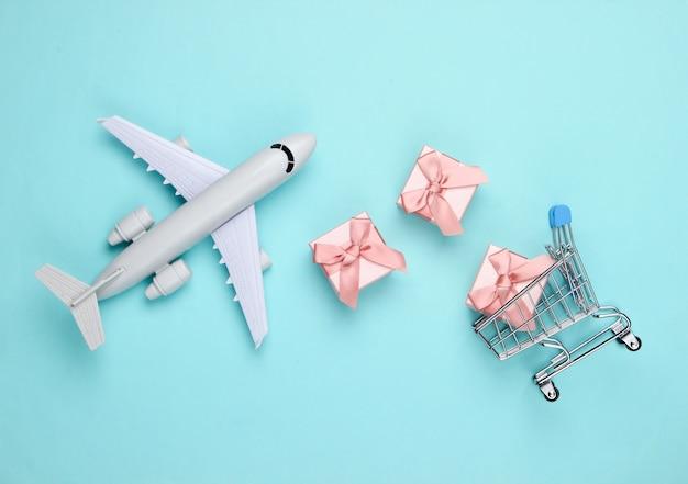 Авиадоставка. фигурка самолета, тележка для покупок и подарочные коробки на синем. плоская планировка.