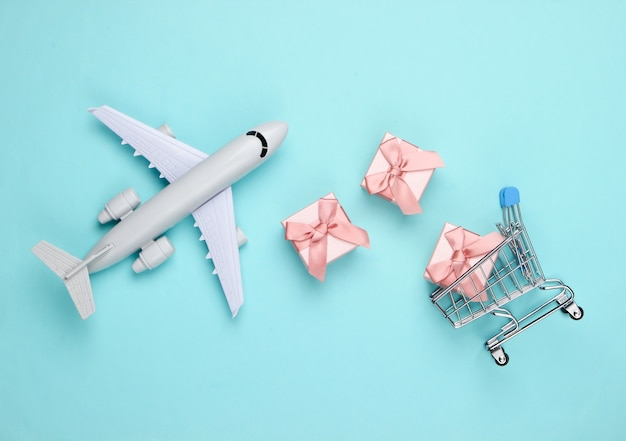 Air delivery. plane figurine, shopping trolley and gift boxes on blue . flat lay.
