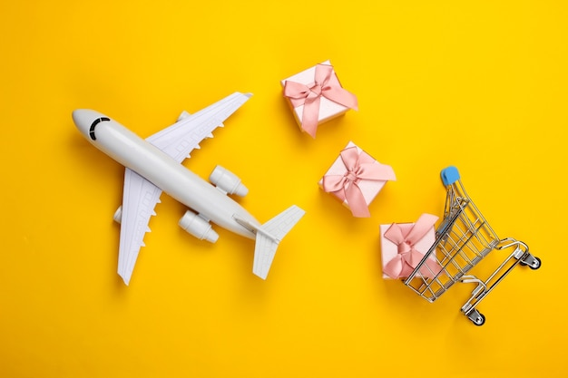 Air delivery. plane figurine, shopping trolley and gift boxes on yellow.