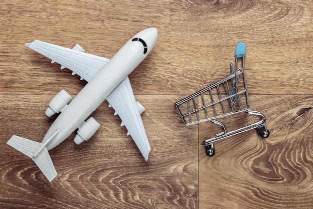 Авиадоставка, шоппинг, логистика. фигурка тележки для покупок, самолета на деревянном полу.