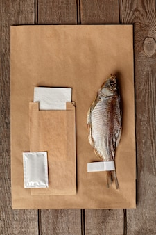 Вяленая плотва с бумажным пакетом из крафт-бумаги, влажной салфеткой и бумажной салфеткой на деревянной поверхности