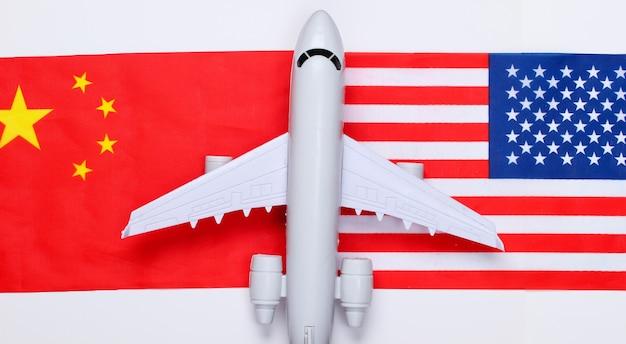 Авиаперелет между странами. фигурка самолета с флагом китая и сша. путешествие по воздуху