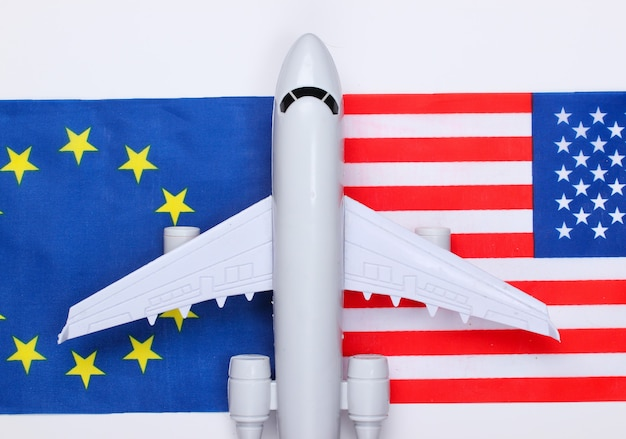 Air flight between countries. a figurine of an airplane with the flag of the european union and the usa. top view
