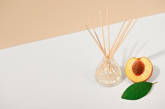 Аромат воздуха с тростниковыми палочками на белом бежевом фоне. натуральный фруктовый аромат, интерьерный аромат. роскошная парфюмерная композиция для дома. освежитель воздуха. скопируйте пространство.