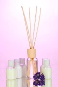 Освежитель воздуха, бутылки и лаванда на розовом