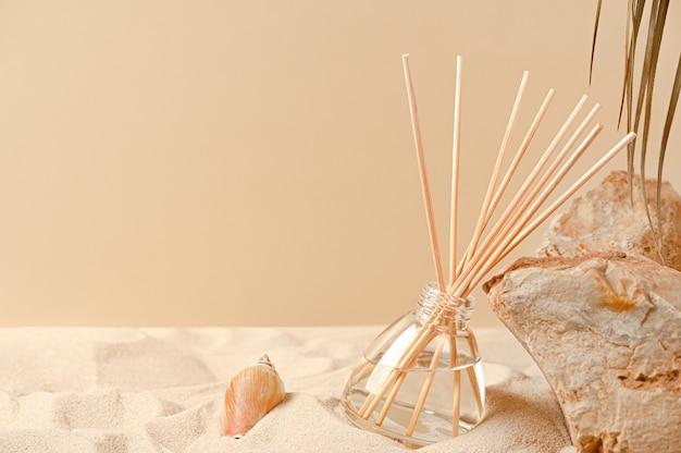 砂、石、貝殻のある自然な背景の芳香剤。リードスティック付きガラスディフューザーの香料組成物。ボトルに入った家庭用芳香剤。スペースをコピーします。