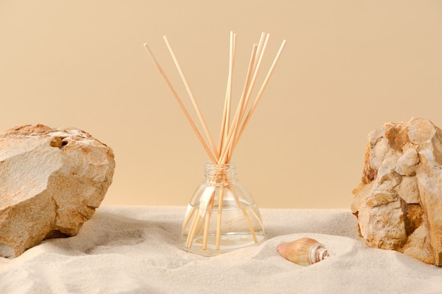 砂、石、貝殻のある自然な背景の芳香剤。リードスティック付きガラスディフューザーの香料組成物。ボトルに入った家庭用芳香剤。