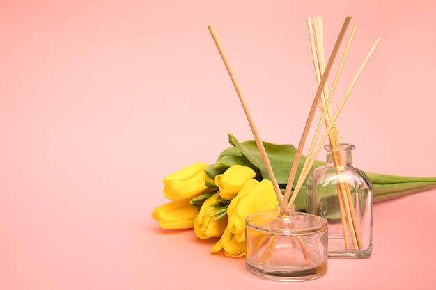 コピースペースのあるピンクの背景に木製のアロマスティックとチューリップの花が付いた芳香剤。家庭での新鮮な空気の概念。クローズアップ写真