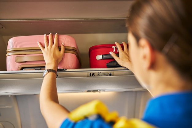 Air hostess fixating two bags on a shelf