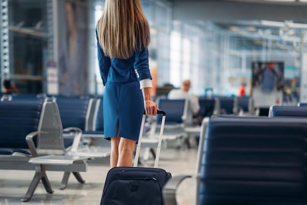 Стюардесса идет между рядами сидений в аэропорту