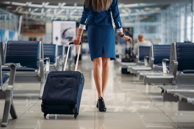 Air hostess going between seat rows in airport