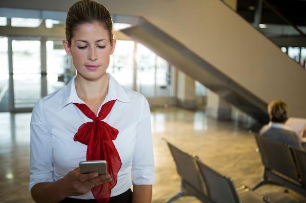 Hostess di volo utilizzando il suo telefono cellulare
