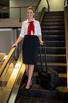 Hostess di volo con borsa trolley sulla scala mobile